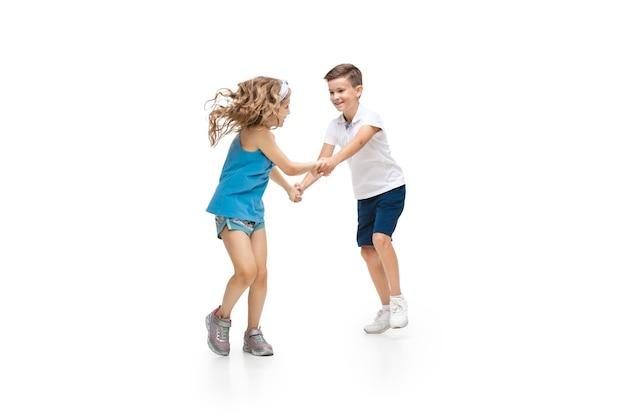 幸せな子供たちがジャンプして白い壁に隔離されて楽しんでいます