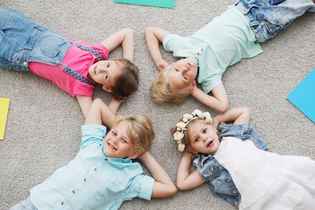 Счастливые дети, лежа на полу дома