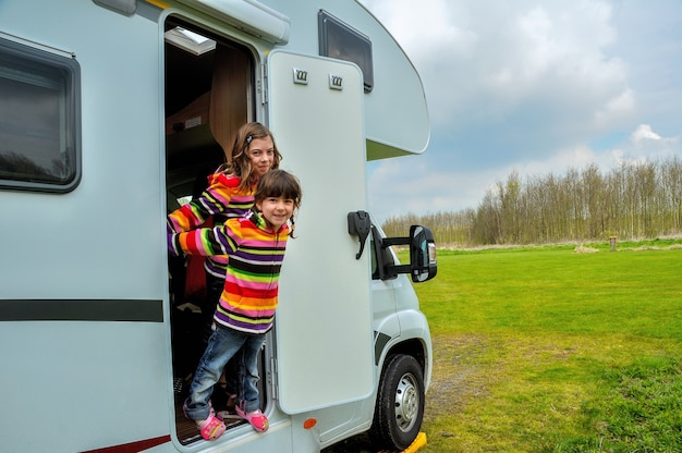 Happy kids near camper rv having fun, family vacation trip in motorhome