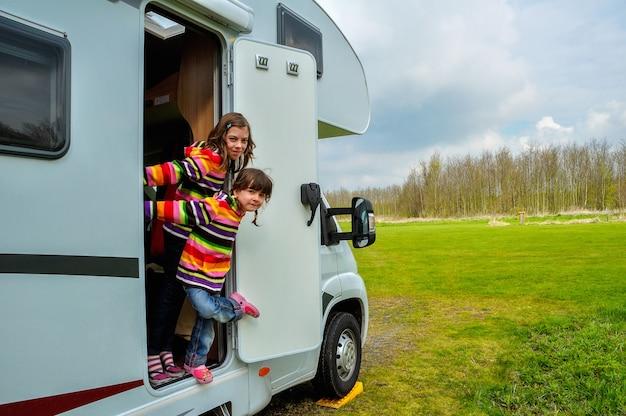 Happy kids near camper (rv) having fun, family vacation trip in motorhome