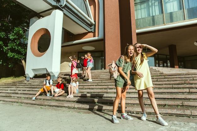 モダンな建物の前で晴れた夏の日に街の通りで遊んで幸せな子供たち。一緒に楽しんでいる幸せな子供やティーンエイジャーのグループ。友情、子供時代、夏、休日の概念。