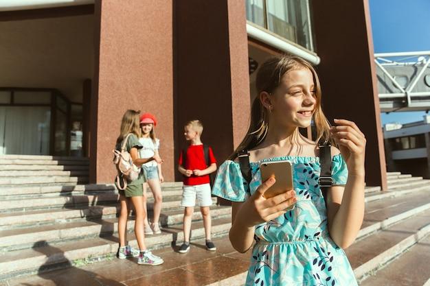 현대 건물 앞 화창한 여름 날에 도시의 거리에서 노는 행복한 아이들. 행복 한 어린이 또는 청소년이 함께 재미 그룹. 우정, 어린 시절, 여름, 휴일의 개념.