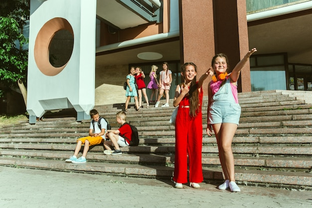 Счастливые дети, играющие на улице города в солнечный летний день перед современным зданием. группа счастливых детей или подростков, весело проводящих время вместе. понятие дружбы, детства, лета, праздников.