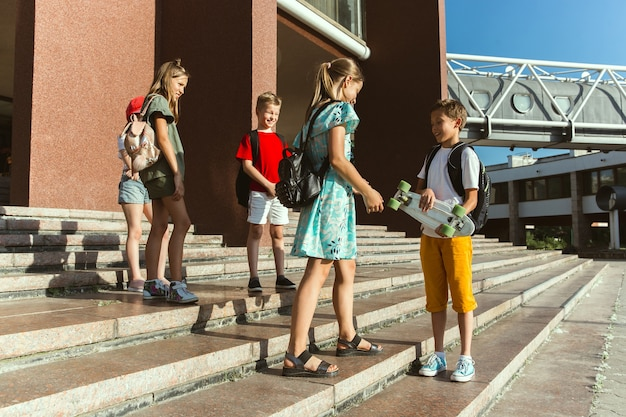 현대적인 건물 앞에서 화창한 여름 날에 도시의 거리에서 노는 행복한 아이들. 행복 한 어린이 또는 청소년이 함께 재미의 그룹입니다. 우정, 어린 시절, 여름, 휴일의 개념.