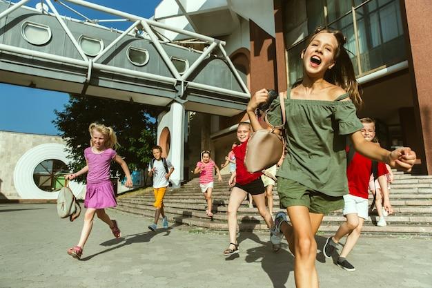 Счастливые дети играют на улице города в солнечный летний день перед современным зданием. группа счастливых детей или подростков, весело проводящих время вместе