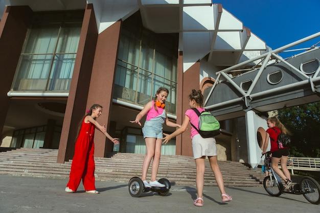モダンな建物の前で晴れた夏の日に街の通りで遊んで幸せな子供たち。一緒に楽しんでいる幸せな子供やティーンエイジャーのグループ