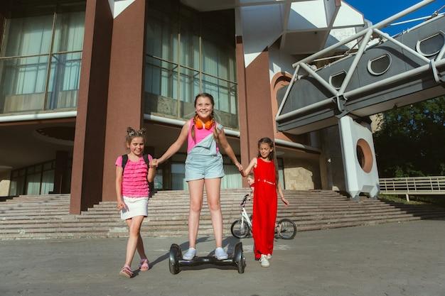 Счастливые дети играют на улице города в солнечный летний день перед современным зданием