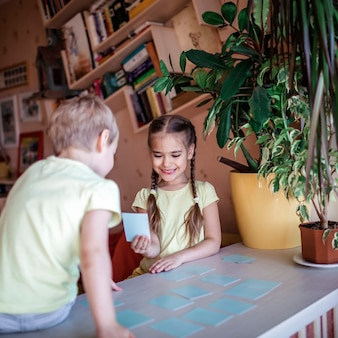 Happy kids playing at board game memo in domestic interior, family values actually, stay at home, life during quarantine