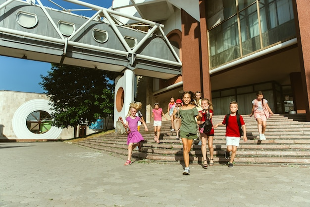 Happy kids playing at city's street in sunny summer's day in front of modern building. group of happy childrens or teenagers having fun together. concept of friendship, childhood, summer, holidays.
