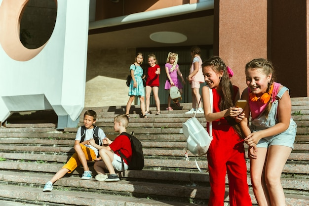 Bambini felici che giocano in strada della città nella soleggiata giornata estiva di fronte a un edificio moderno. gruppo di bambini felici o adolescenti che hanno divertimento insieme