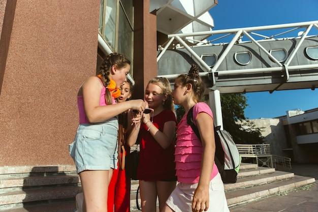 Bambini felici che giocano in strada della città nella soleggiata giornata estiva di fronte a un edificio moderno