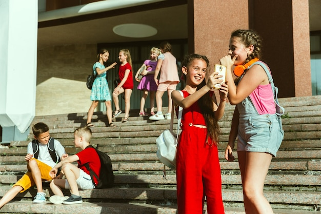 Happy kids playing at city's street in sunny summer's day in front of modern building