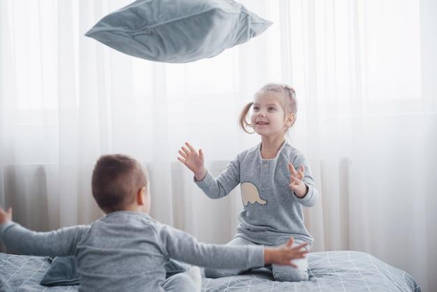 Счастливые дети, играющие в белой спальне. маленький мальчик и девочка, брат и сестра играют на кровати в пижаме. пижамы и постельные принадлежности для малышей и малышей. семья дома.