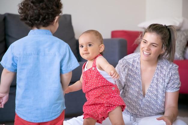 Bambini felici che giocano in soggiorno con mamma bionda. bambina sveglia in piedi e guardando il ragazzo riccio. madre amorevole sorridente che guarda i bambini. famiglia al chiuso, weekend e concetto di maternità