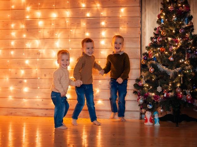 クリスマスツリーの近くで遊ぶ幸せな子供たち
