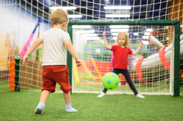 Happy kids playing soccer indoors