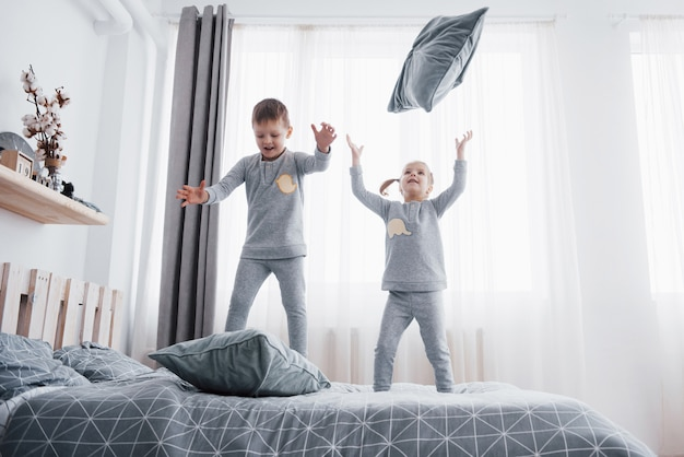 Happy kids playing in white bedroom. little boy and girl, brother and sister play on the bed wearing pajamas. nightwear and bedding for baby and toddler. family at home