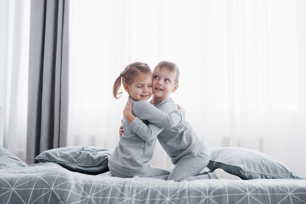 Happy kids playing in white bedroom. little boy and girl, brother and sister play on the bed wearing pajamas.