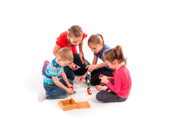 白で隔離のビルディングブロックで遊んで幸せな子供たち。チームワーク、創造性の概念。