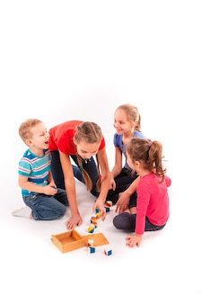 Happy kids playing with building blocks isolated on white. team work, creativity concept.