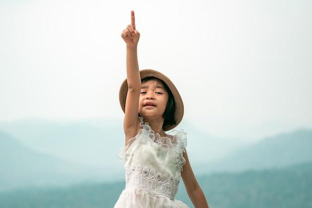 幸せな子供が空を指す