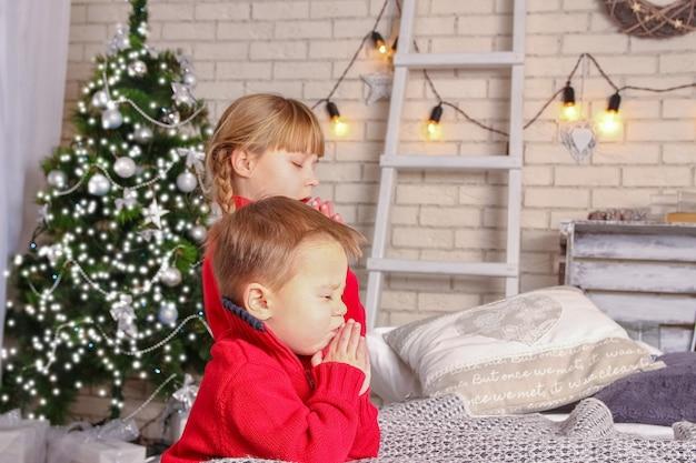 クリスマスのために家で祈る幸せな子供たち
