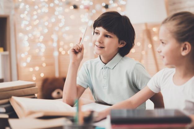 幸せな子供たちは机で一緒にクラスの準備をします。
