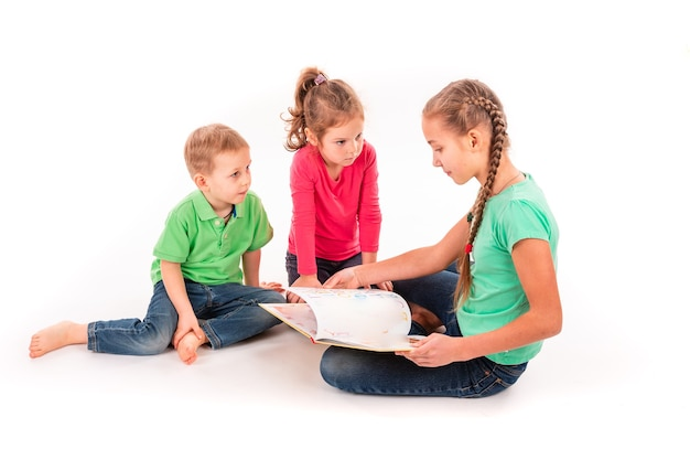 Happy kids reading a book isolated on white. team work, creativity concept.