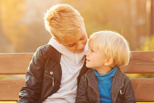 Счастливые дети, сидя на скамейке. старший брат обнимает младшего брата на открытом воздухе. семья, отношения и дети