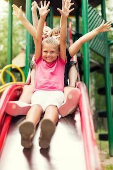 Bambini felici scivolano sul parco giochi