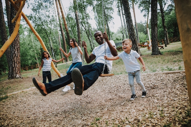 Happy kids swinging parents in park on swings