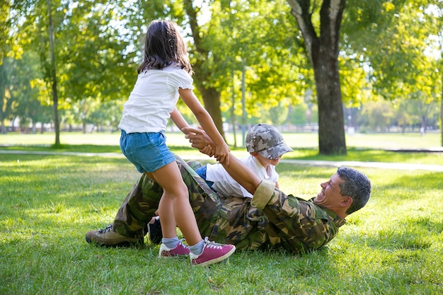 Happy kids and their military dad lying and playing on grass in park. girl pulling fathers hand. family reunion or returning home concept