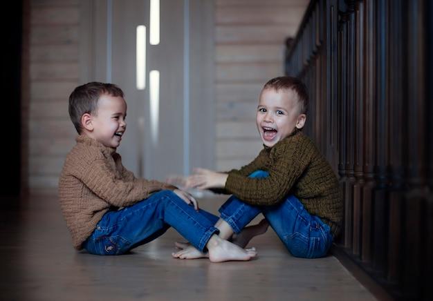 幸せな子供たちの双子の兄弟が家で遊んでいます