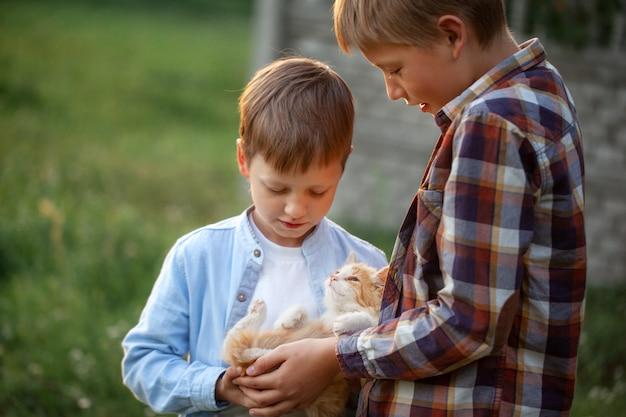 Счастливые дети с котенком в руках в природе на лето.