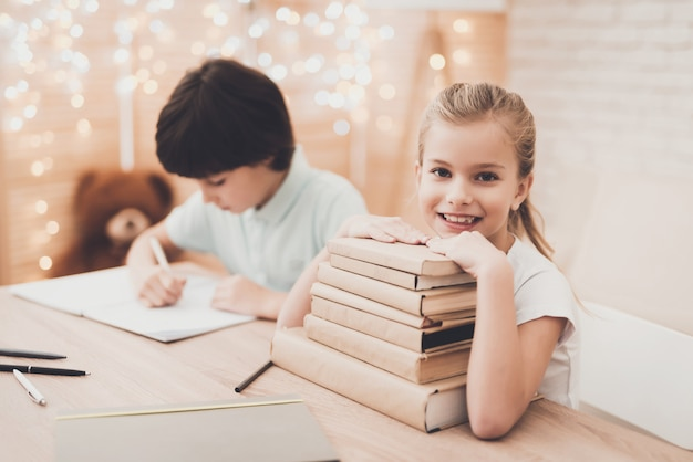 Happy kids with stacked textbooks at the desk