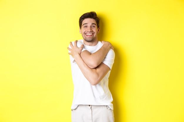 黄色の背景に喜んで立って、自分を抱きしめて笑って幸せな親切な男。コピースペース