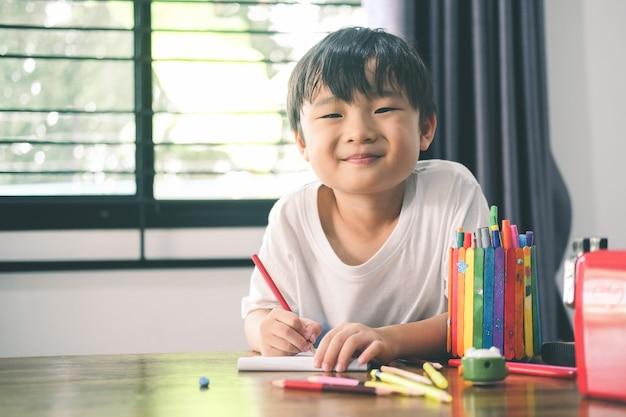행복한 유치원 소년은 집에서 그림을 그리고 학습합니다. 교육, 원격 학습 개념입니다.