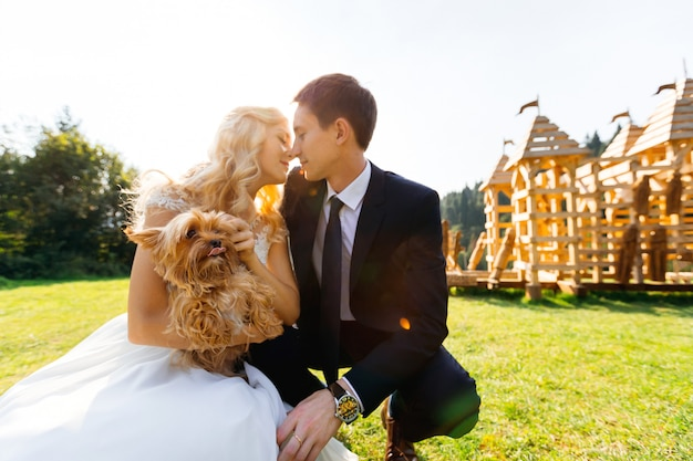 Happy kissing couple hold a small yorkshire terrier on a green
