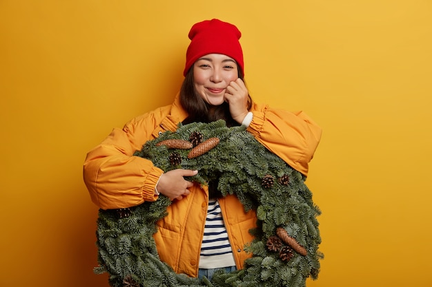 Happy korean woman dressed in winter outerwear, expresses sincere emotions, holds beautiful spruce wreath, stands against yellow background indoor.