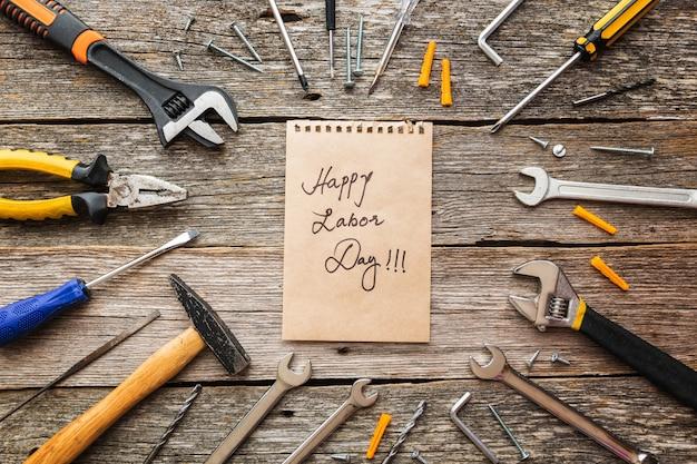 幸せな労働者の日のグリーティングカードまたは背景。素朴な木製の背景に建設ツール。