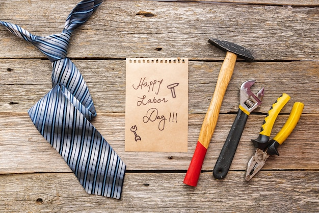 Happy labor day on a piece of paper with tie and construction tools on wooden background