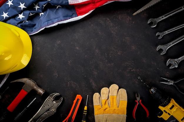 幸せな労働者の日いくつかのエンジニアコンストラクター作業ツールとアメリカの国旗