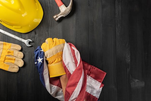 С днем труда. несколько перчаток рабочих инструментов инженеров-конструкторов держат в руках американский флаг