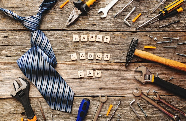 Happy labor or father day on wooden blocks with tie and construction tools on wooden background