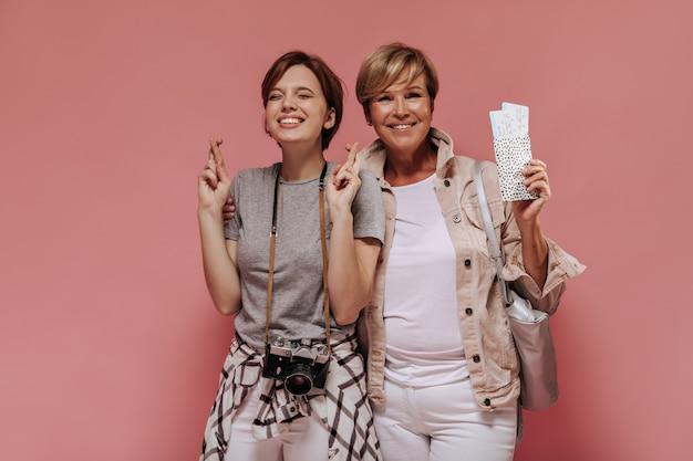 短い髪型と魅力的な笑顔でトレンディな衣装を抱き締め、指を交差させ、ピンクの背景にチケットを持っている幸せな女性。