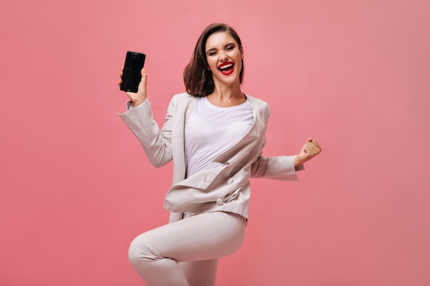 Happy lady in beige suit poses with phone on pink background. joyful girl in office dress and with red lips holds smartphone.