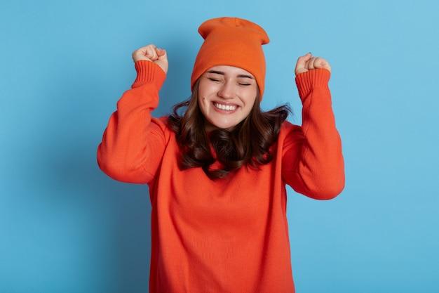 Happy lady dresses orange jumper and cap, keeps eyes closed and making hooray gesture, raising hands, feels very happy