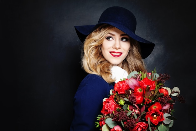 テキストのコピースペースと背景に花を持つ幸せな女性のファッションモデル