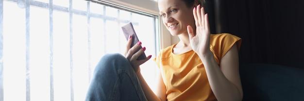 Счастливая дама приветствует во время видеозвонка с помощью смартфона дома возле окна