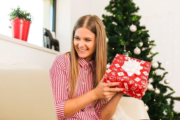 Happy lady holding gift box near christmas tree